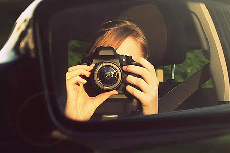Frau fotografiert sich selber im Autospiegel