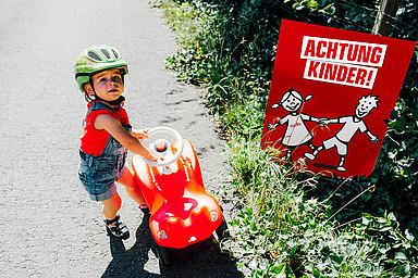 Kind mit Bobbycar vor Achtung Kinder Plakat!