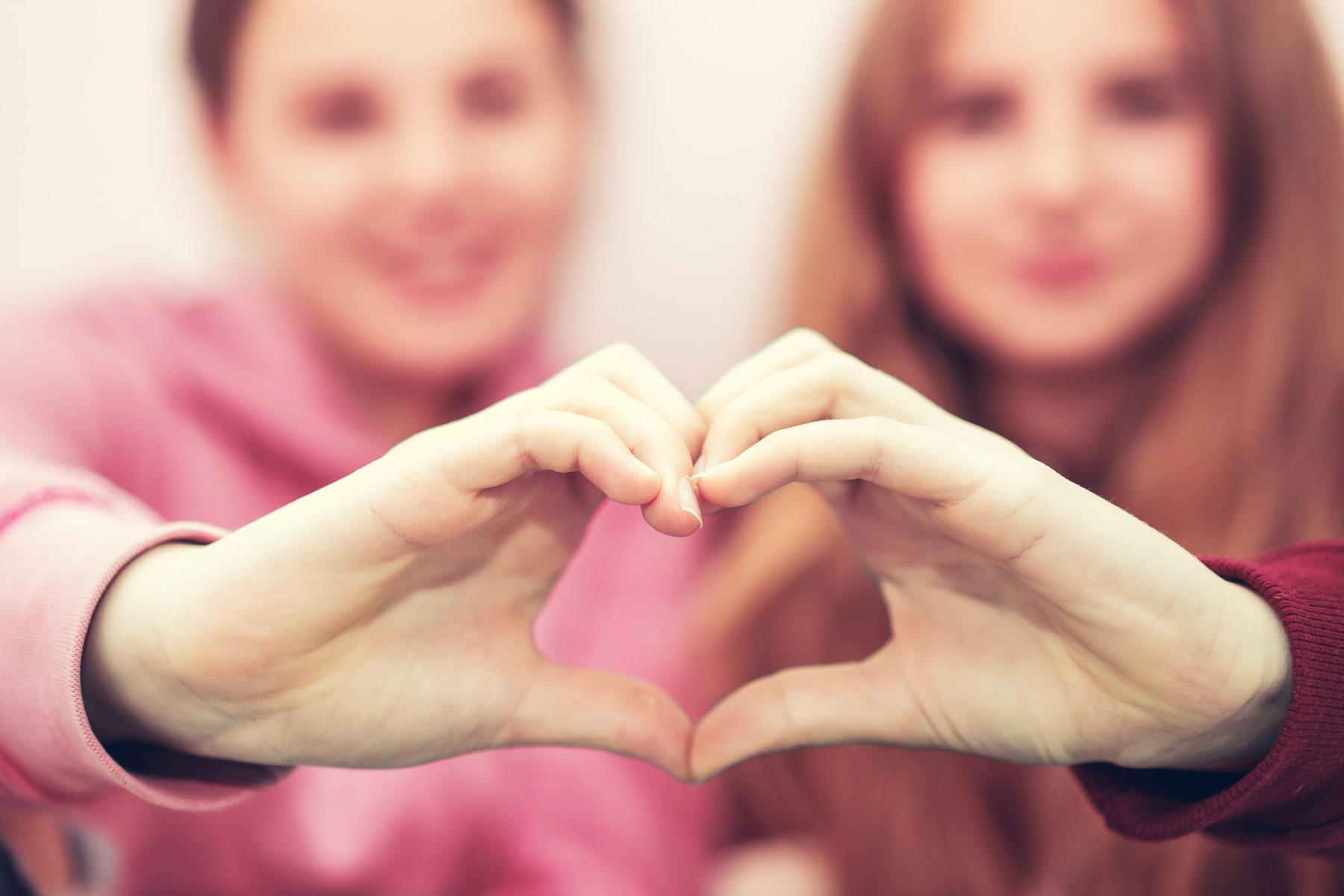 Freundinnen zeigen ein Herz